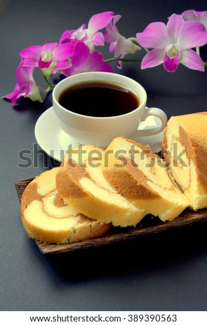 chocolate Slice swiss roll on wooden plate served with a cup of coffee and black background with orchid flower  - stock photo