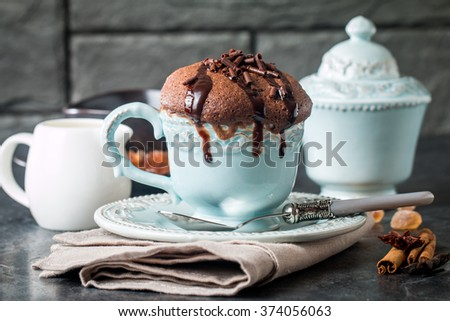 Chocolate souffle with  chocolate glaze in a cup on grey background - stock photo
