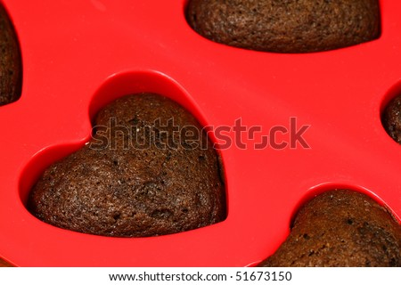 Chocolate sponge cake hearts in red silicone mold. Valentine sweet - stock photo