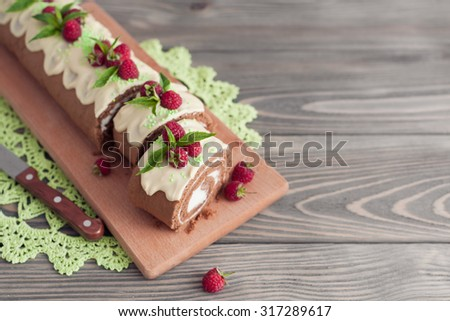 Chocolate sponge roll with with cream and raspberries on wooden background - stock photo