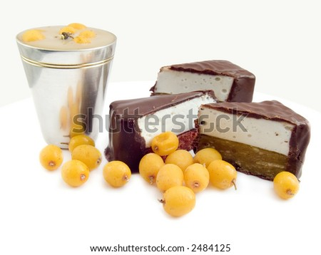 Chocolate sweets a silvered wine-glass with liquor and the frozen berries of sea-buckthorn berries isolated on a white background - stock photo