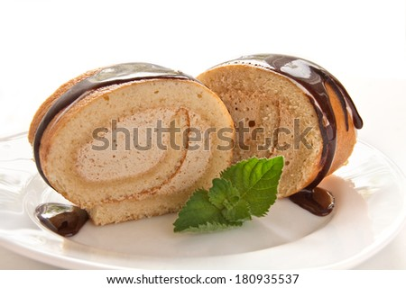 Chocolate swiss roll cake with mint on the white background - stock photo