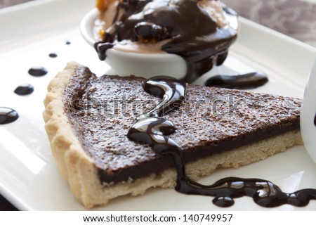 Chocolate tart slice and ice cream with melted dripping chocolate sauce. - stock photo