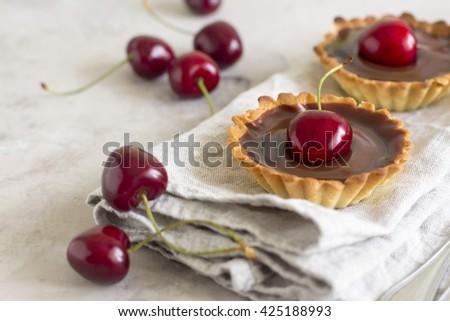 chocolate tart with cherry. Homemade mini cherry tart with chocolate ganache on gray background - stock photo