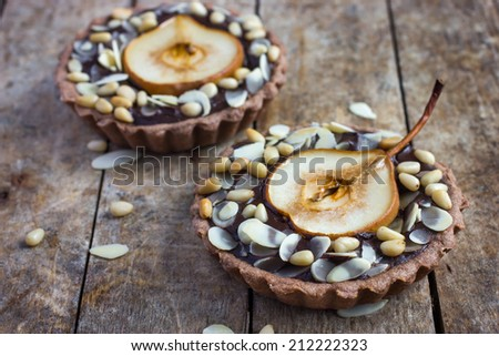 chocolate tartlets with pear and nuts on a wooden background - stock photo