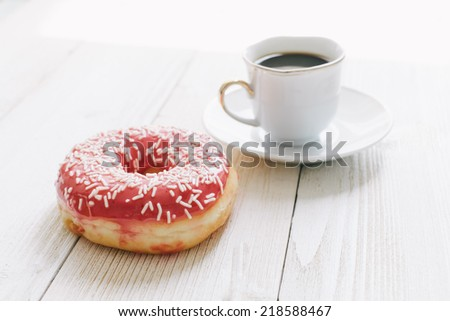 Chocolate top donut and black coffee on a table top - stock photo