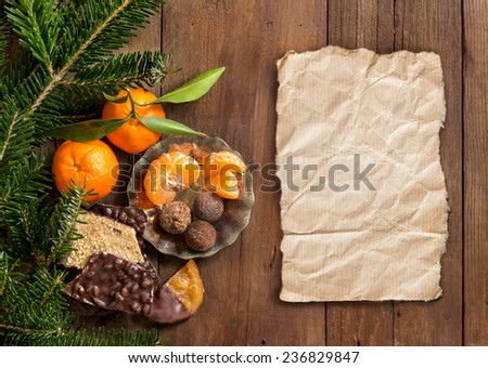 Chocolate, truffles and tangerines with fir and craft paper - stock photo