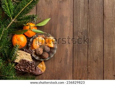 Chocolate, truffles and tangerines with fir on a wooden table - stock photo