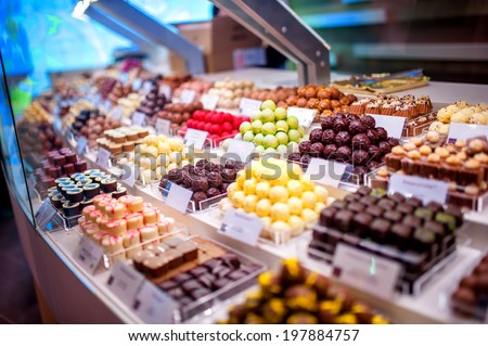 chocolate truffles, candies and sweets store on showcase in factory store. Chocolate bit sized for sale in local chocolate store - stock photo