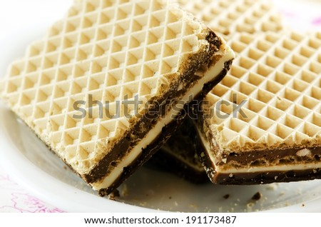 Chocolate waffers on a white plate. - stock photo