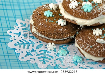 chocolate whoopie pie with snowflake candy on snowflake doily - stock photo
