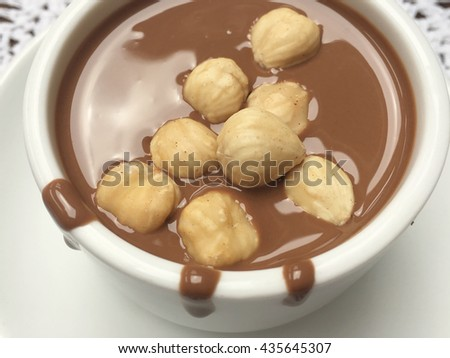 Chocolate with hazelnuts. White cup for your text. Milk chocolate. Liquid milk chocolate.  - stock photo