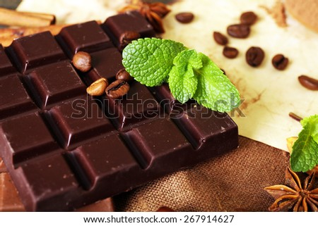 Chocolate with mint, spices and coffee beans on table, closeup - stock photo