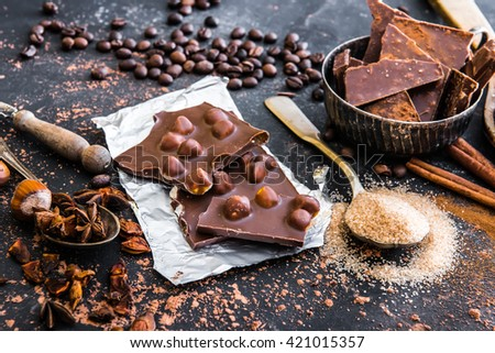 Chocolate with nuts and spices in the spoons on a dark table - stock photo