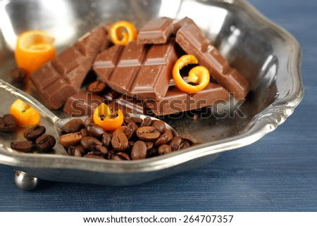 Chocolate with orange peels and coffee beans in metal tray on wooden table, closeup - stock photo