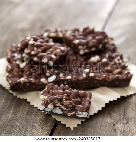 chocolate with puffed rice bar on wooden table, close up - stock photo