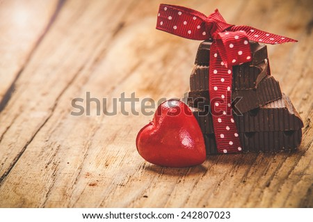 Chocolate with ribbon and heart on St. Valentine's day love. - stock photo