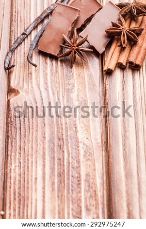 Chocolate with spices - anise, vanilla, cinnamon on the wooden background - stock photo