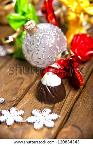 chocolates and Christmas decorations for the Christmas tree on a wooden table. Christmas collection of sweets - stock photo