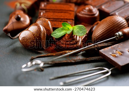 Chocolates. Chocolate sweets. Assortment of fine chocolates in dark and milk chocolate with vanilla and mint. Praline Chocolate - stock photo