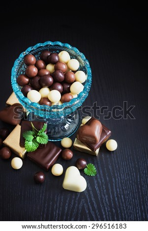 chocolates in a glass bowl on a black wooden background. festivals and events.top view - stock photo