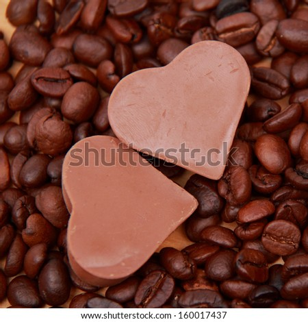 Chocolates in the form of heart with lots of coffee beans over light brown wooden background/delicious chocolate heart symbol candies and dark brown coffee beans - stock photo