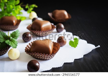 chocolates in the shape of hearts on a black wooden background. festivals and events.selective focus - stock photo