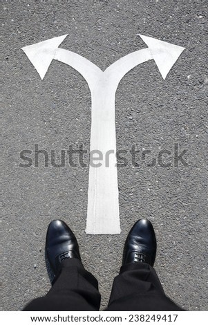 choice concept - business man walking with arrow on the road - stock photo
