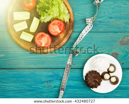 Choice of food: diet on vegetables or cake and candy. And centimeter tape on blue wooden desk - stock photo