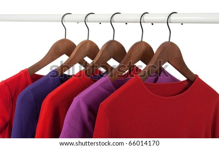Choice of red and purple casual shirts on wooden hangers, isolated on white. - stock photo