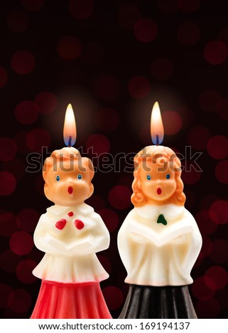 Choir Boy and Girl Candles isolated on a dark background. - stock photo