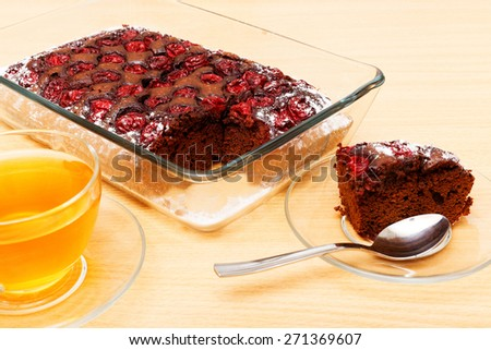 Chokolate cake with cherry and cup of green tea - stock photo