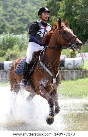 CHONBURI, THAILAND - JULY 27:Korntawat Samram of Thailand with Maximus F. in action during 1st FEI Asian Eventing Championships 2013 at Thai Polo&Equestrian Club on July 27, 2013 in Chonburi, Thailand. - stock photo