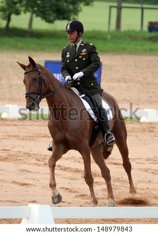 CHONBURI, THAILAND - JULY 26:Supap Khaw-Ngam of Thailand with Ardbohill Lad in action during 1st FEI Asian Eventing Championships 2013 at Thai Polo&Equestrian Club on July 26, 2013 in Chonburi, Thailand. - stock photo