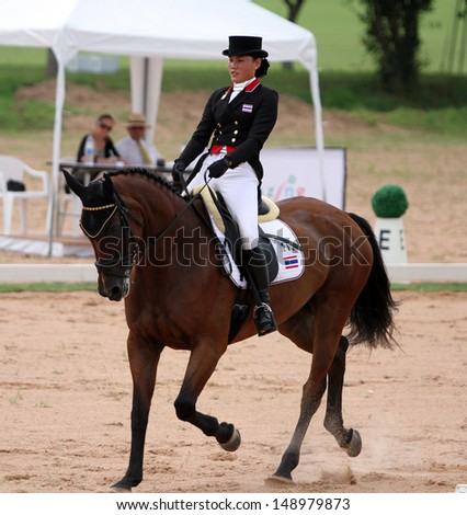 CHONBURI, THAILAND - JULY 26:Thanaporn Chavatanont of Thailand with Painters Peer in action during 1st FEI Asian Eventing Championships 2013 at Thai Polo&Equestrian Club on July 26, 2013 in Chonburi, Thailand. - stock photo