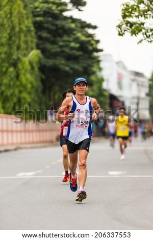 CHONBURI, THAILAND - 20 JULY 2014 - Unidentified athletes run in twelfth Walk and Run Phanat Nikhom Supper Mini-marathon race at Phanat Nikhom district, Chonburi, Thailand. - stock photo