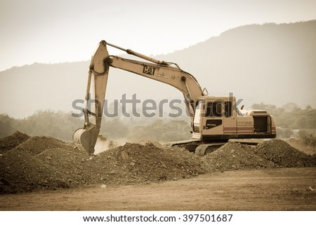 CHONBURI,THAILAND - MARCH 25,2016 : The yellow excavator is working with soil and dusty at new road building site in countryside. - stock photo