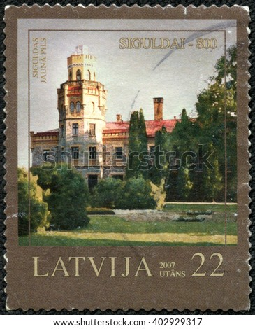 "CHONGQING, CHINA - April 17, 2014:A stamp printed in Latvia from the ""800th anniversary of Sigulda "" issue shows New Castle, circa 2007. - stock photo"