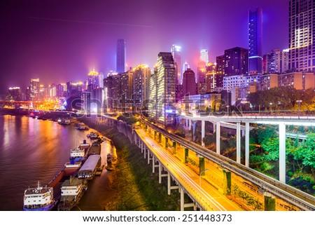Chongqing, China riverside cityscape at night. - stock photo