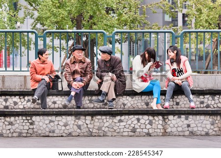 CHONGQING-NOVEMBER 4, 2014. Chinese elderly and youngsters. Government report forecasts China becomes the world's most aged society in 2030, by 2050 its older population will swell to 330 million. - stock photo