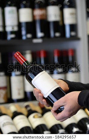 Choose and buy a bottle of wine in a specialty store - stock photo