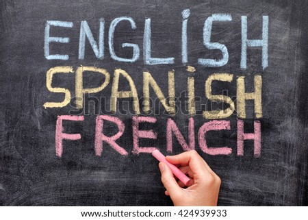 Choose your language. Hand drawing English, Spanish, French on blackboard. Close up. - stock photo