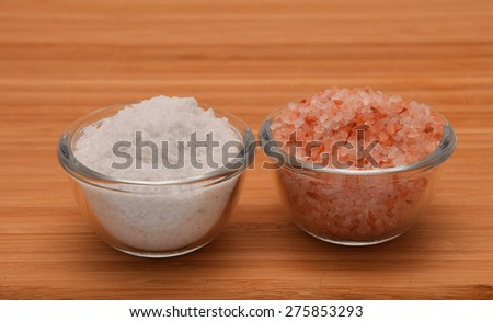 Choose your salt - Himalayan or rock salt (side view, close to each other) on wooden bamboo background - stock photo