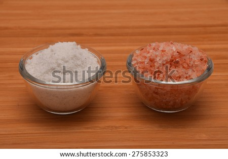 Choose your salt - Himalayan or rock salt (side view, distanced from each other) on wooden bamboo background - stock photo