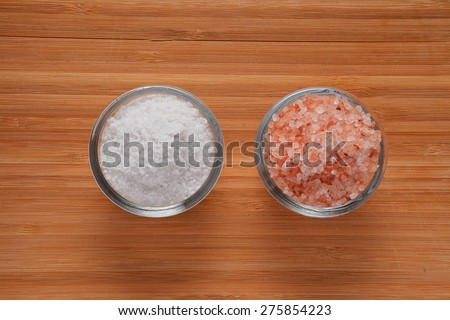 Choose your salt - Himalayan or rock salt (top view, point of view) on wooden bamboo background - stock photo