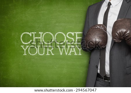 Choose your way on blackboard with businessman wearing boxing gloves - stock photo