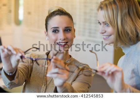 Choosing glasses at the optician - stock photo
