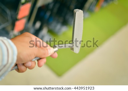 Choosing golf club on retail shop background. Closeup on hand - stock photo