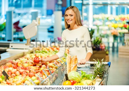 Choosing healthy food. Smiling young woman holding apple and looking at camera while standing in a food store  - stock photo