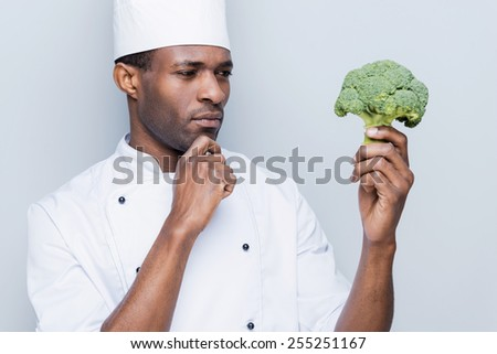 Choosing the best ingredient for his meal. Thoughtful young African chef in white uniform holding broccoli and looking at it while standing against grey background - stock photo